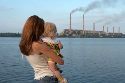 """""""care future"""" concept. Young mother with her kids are looking at the chimney-stalks polluting an air"""